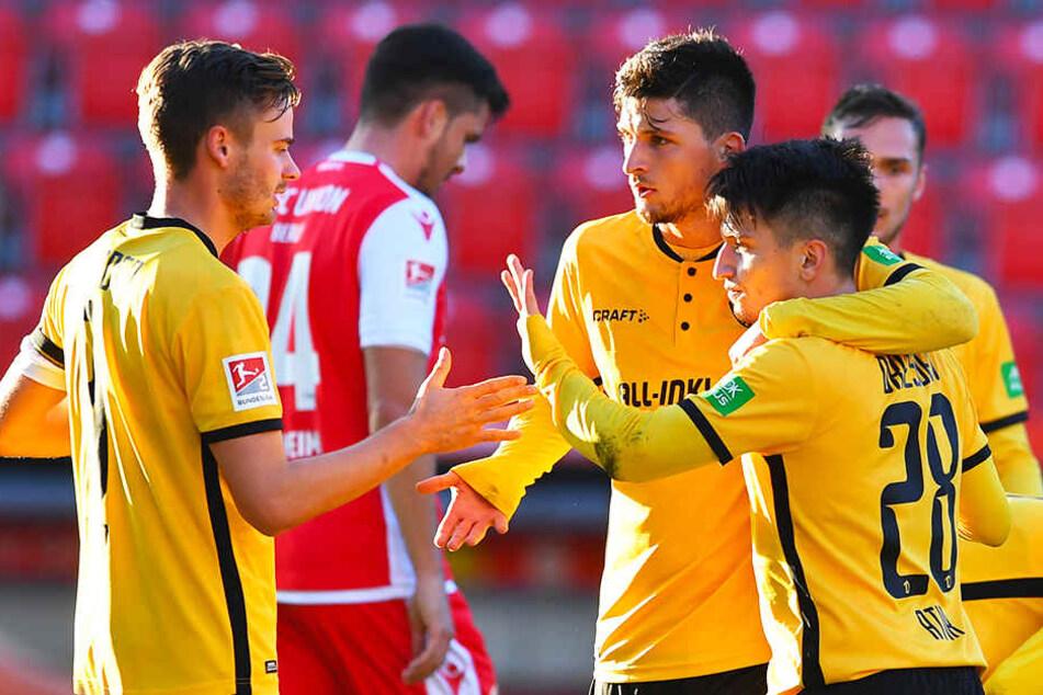 Dynamos Spieler Lucas Röser (l.) und Jannis Nikolaou (Zweiter von r.) beglückwünschen Baris Atik (r.) zu dessen 1:1-Ausgleichstreffer.