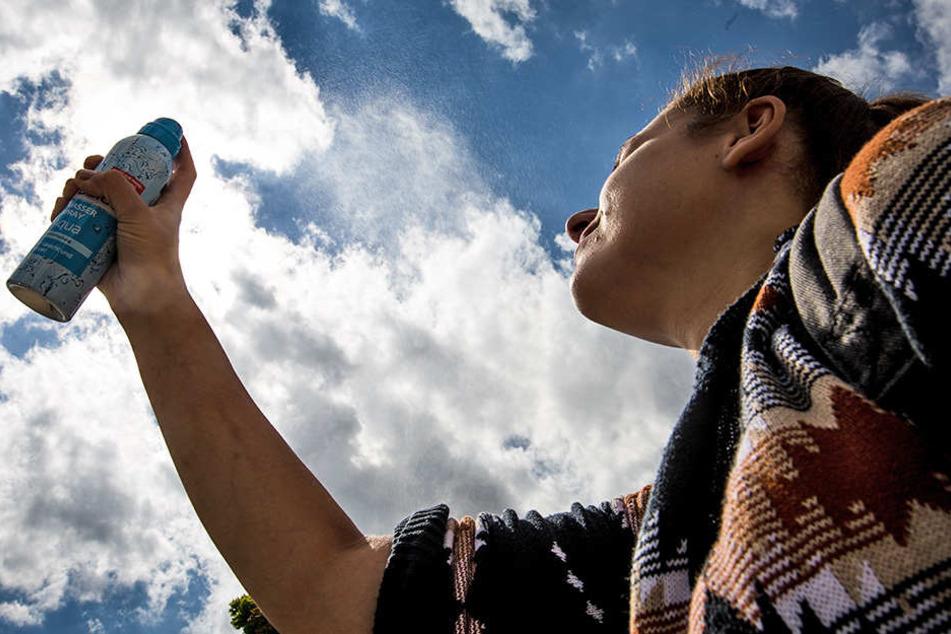 Eine junge Frau sprüht sich bei warmen Temperaturen zur Erfrischung Wasserspray ins Gesicht.