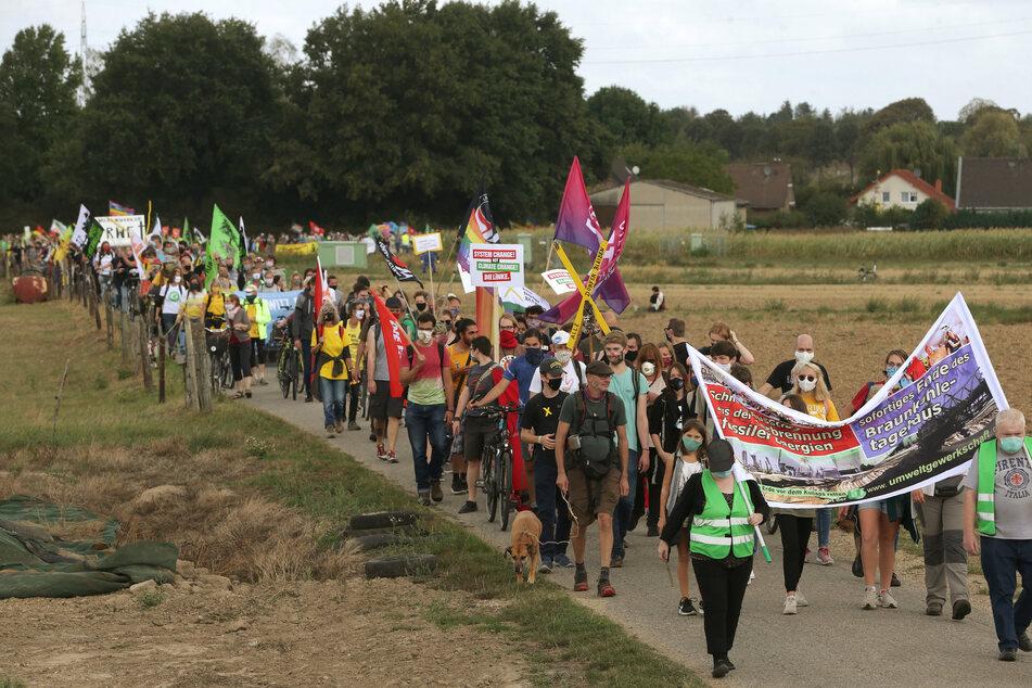 """Der Demonstrationszug geht in Richtung Lutzerath . Ein bundesweites Bündnis von Umweltverbänden und Klimagruppen will """"gegen die Zerstörung der gefährdeten Dörfer und für Klimagerechtigkeit zu protestieren""""."""