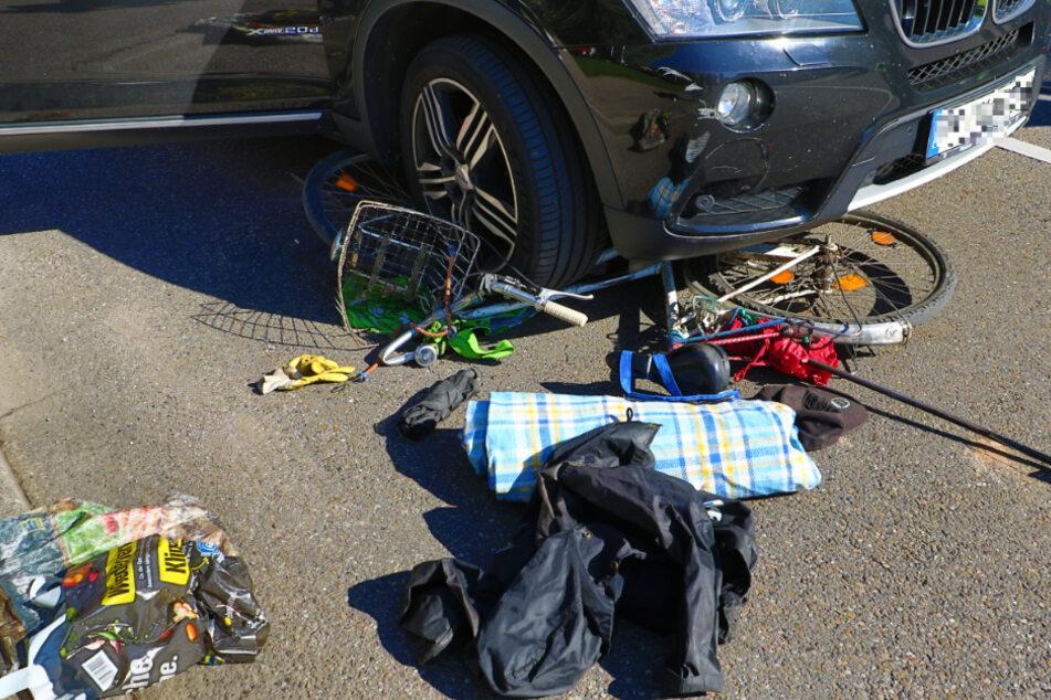 Das Fahrrad liegt unter dem Auto auf der Straße. Ein Fahrradfahrer wurde bei dem Unfall schwer verletzt.