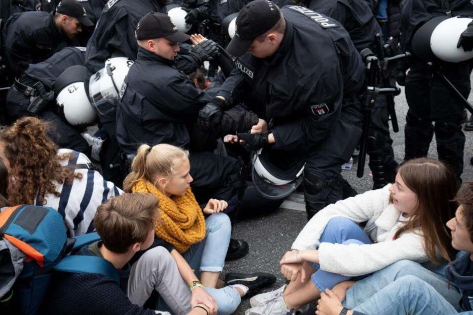 Polizisten lösen eine Sitzblockade auf dem Stephansplatz auf.