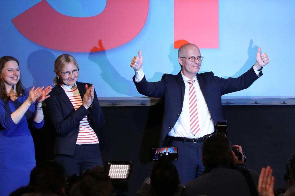 Peter Tschentscher (rechts) jubelt nach der ersten Prognose auf der Wahlparty seiner Partei zusammen mit seiner Ehefrau Eva-Maria (m) und Melanie Leonhard, SPD.