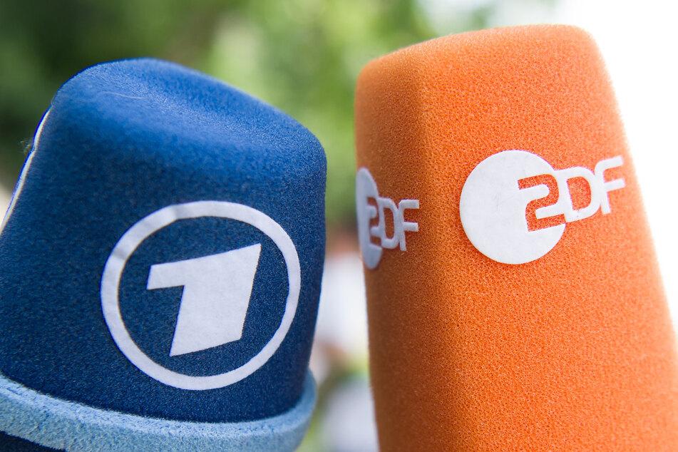 Fernsehmikrofone mit den Logos von ARD und ZDF werden nebeneinander gehalten.