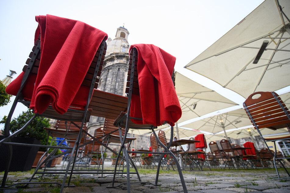 Rote Decken liegen auf Stühlen der Außengastronomie eines Restaurants auf dem Neumarkt vor der Frauenkirche für Gäste bereit.