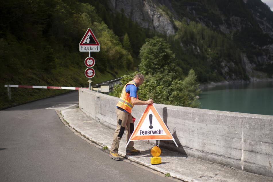 Ein Mann errichtet an der Staumauer am Gigerwaldsee eine Straßensperre für die Feuerwehr.