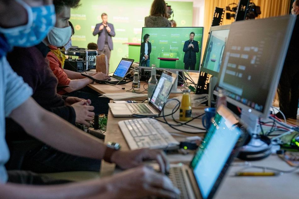 Menschen mit Mund-Nase-Schutz arbeiten an Rechnern in der Grünen-Parteizentrale während der Eröffnung des Online-Parteitages der Grünen.