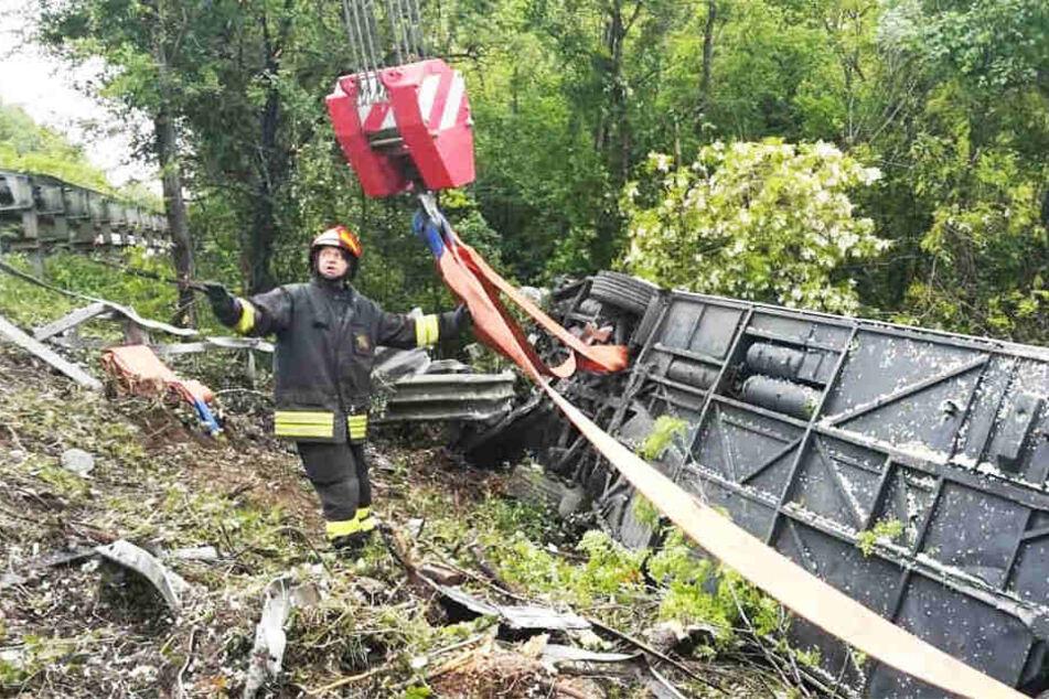Fotos der Feuerwehr zeigen den verunglückten Bus an einem Abhang in der Böschung.