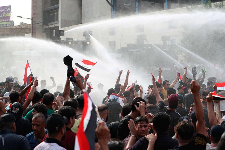 Irakische Sicherheitskräfte gehen mit Wasserwerfern gegen Demonstranten vor, die gegen Korruption und politischen Stillstand auf dem Tahrir-Platz demonstrieren.