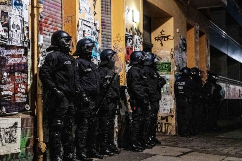 Polizeibeamte stehen bei einer Razzia in der Rigaer Straße in Berlin-Friedrichshain vor einem Haus. (Symbolbild/Archivbild)