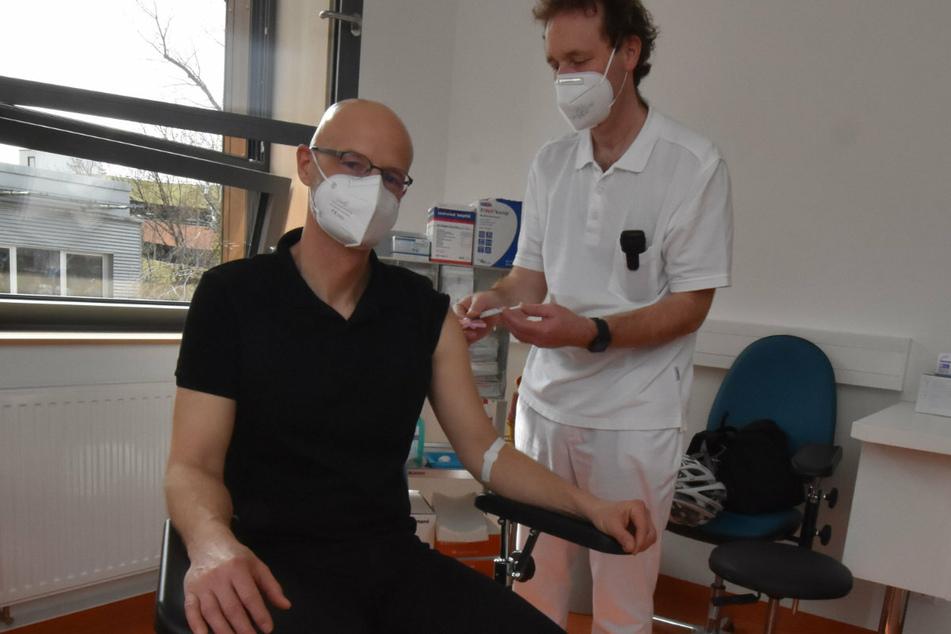 Prof. Gunnar Folprecht (r.), Leiter des Fachbereichs Onkologie des Uniklinikums Dresden, impft Peer Schmidt. Der Leukämiepatient wird seit 2016 nach erfolgreicher Stammzelltransplantation am Dresdner Uniklinikum ambulant nachbetreut.