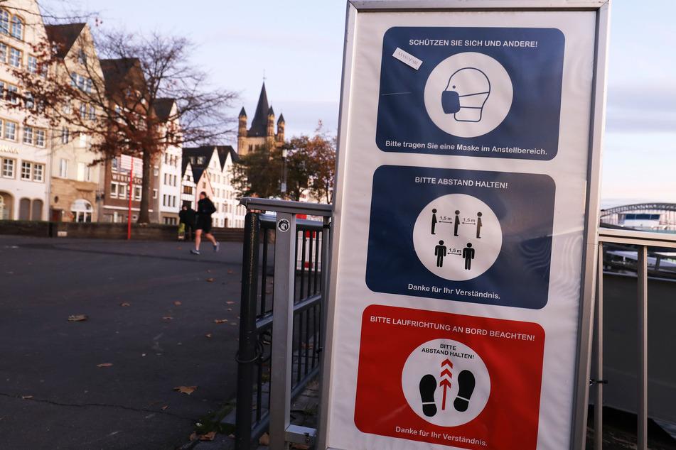 Ein Schild mit Hinweisen auf die Hygieneregeln steht am Rheinufer in Köln. Die Regierung will mit einem Teil-Lockdown im Monat November die Corona-Infektionszahlen in Deutschland senken.