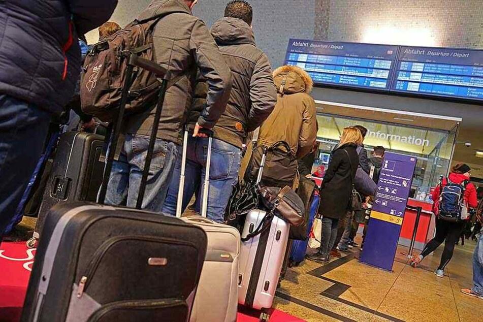 Bahnreisende stehen im Kölner Hauptbahnhof und informieren sich, wie und wo sie die Nacht verbringen können