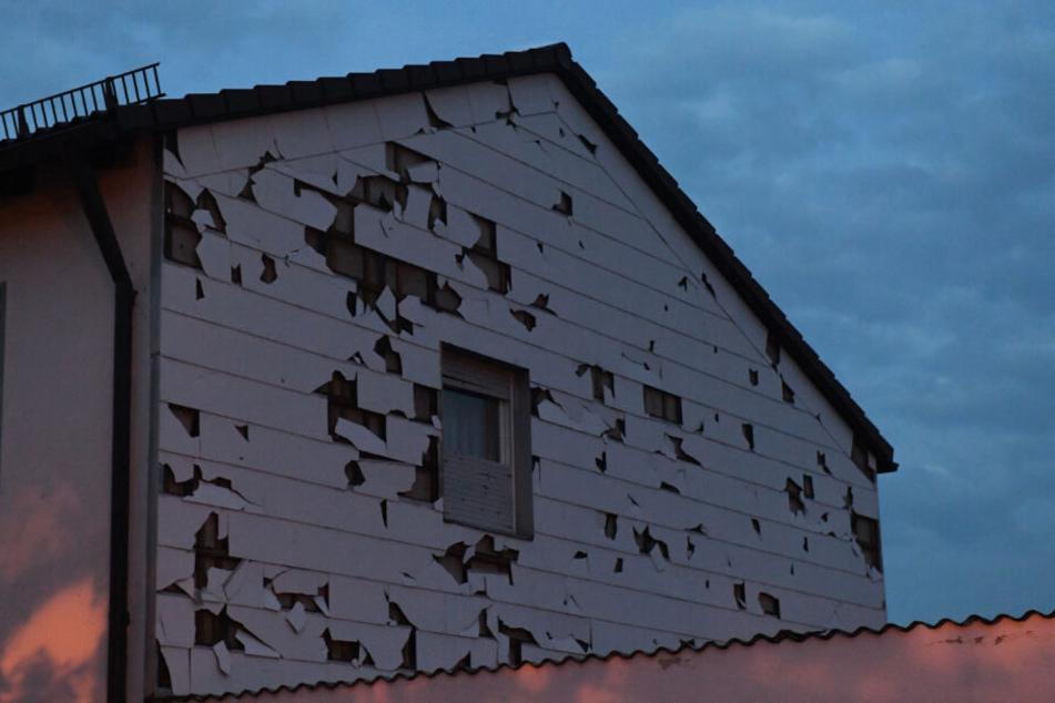 Eine durch Hagel bei einem Unwetter beschädigte Verkleidung einer Hauswand in Germering.