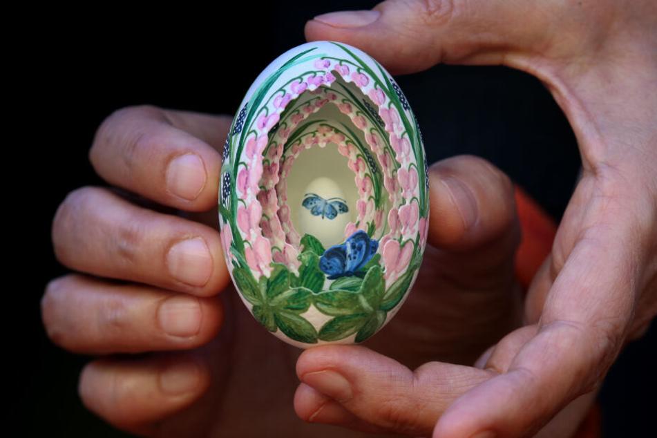 Eine Frau hält im Allgäuer Ostereier-Museum ein bemaltes Osterei in das drei weitere kleinere Eier eingefügt sind.