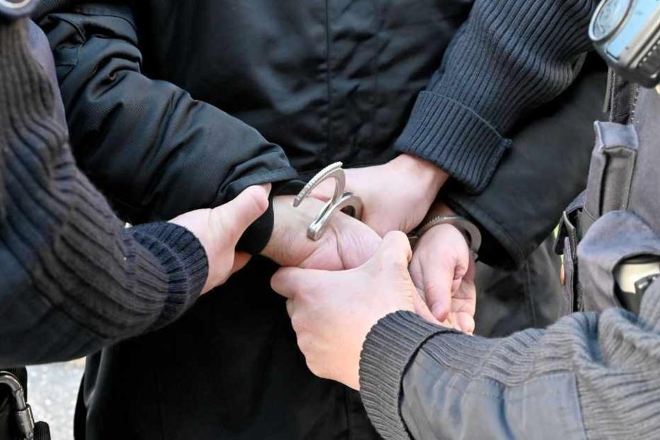 Polizisten legen einem Tatverdächtigen Handschellen an.
