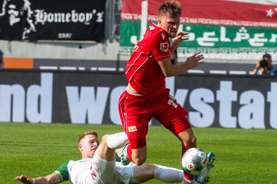 Unions Marius Bülter (oben) setzt sich gegen Augsburgs André Hahn durch.