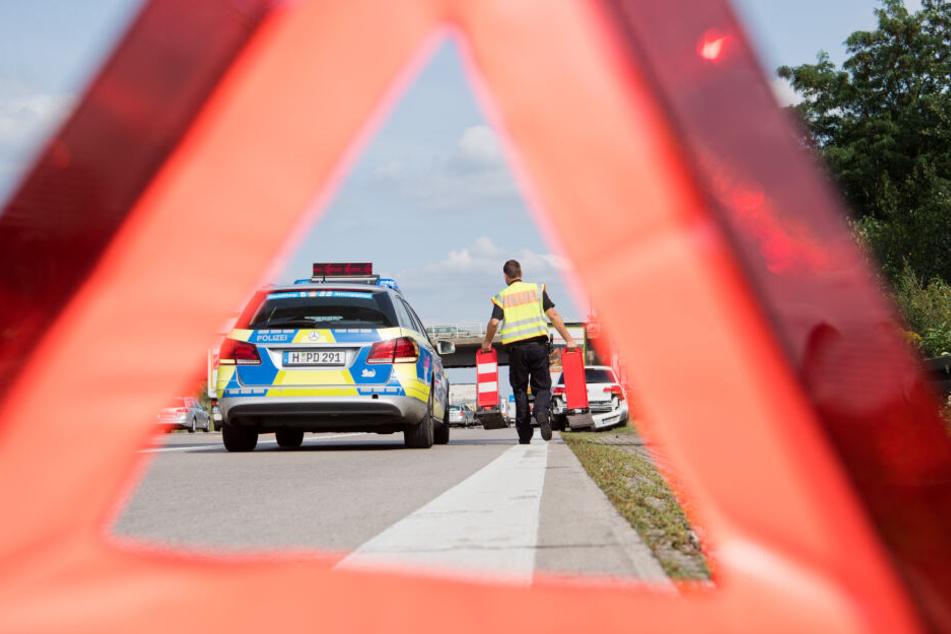 Ein Beamter der Autobahnpolizei sichert eine Unfallstelle. (Symbolbild)