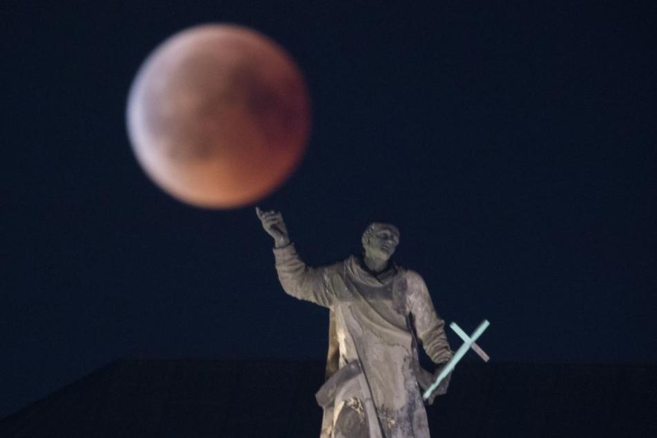 Spektakuläre Bildkomposition: Der Vollmond ist hinter einer Mattielli-Statue auf der katholischen Hofkirche in Dresden zu sehen.