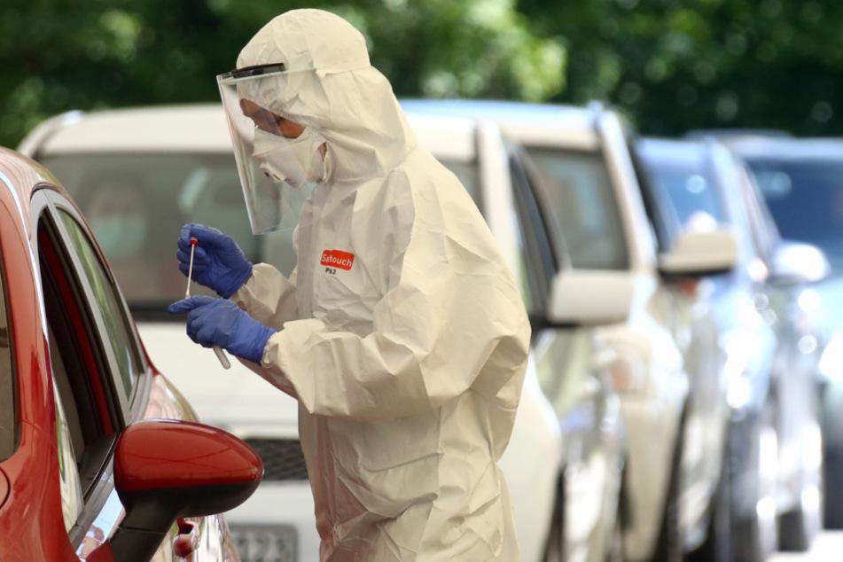 Gesundheitspersonal sammelt Proben in einer behelfsmäßigen COVID-19-Teststation.