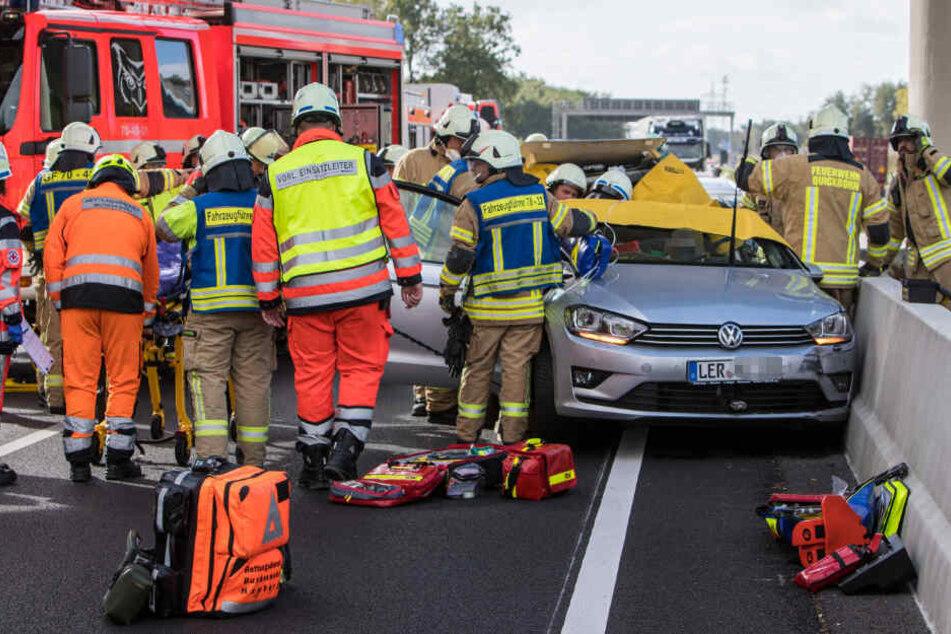 Feuerwehrleute befreien einen eingeklemmten Insassen aus dem Unfallfahrzeug.