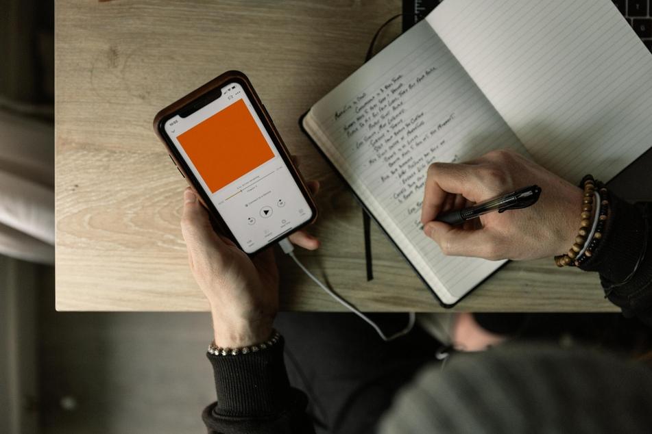 Eine Person hört einen Podcast und macht sich Notizen.