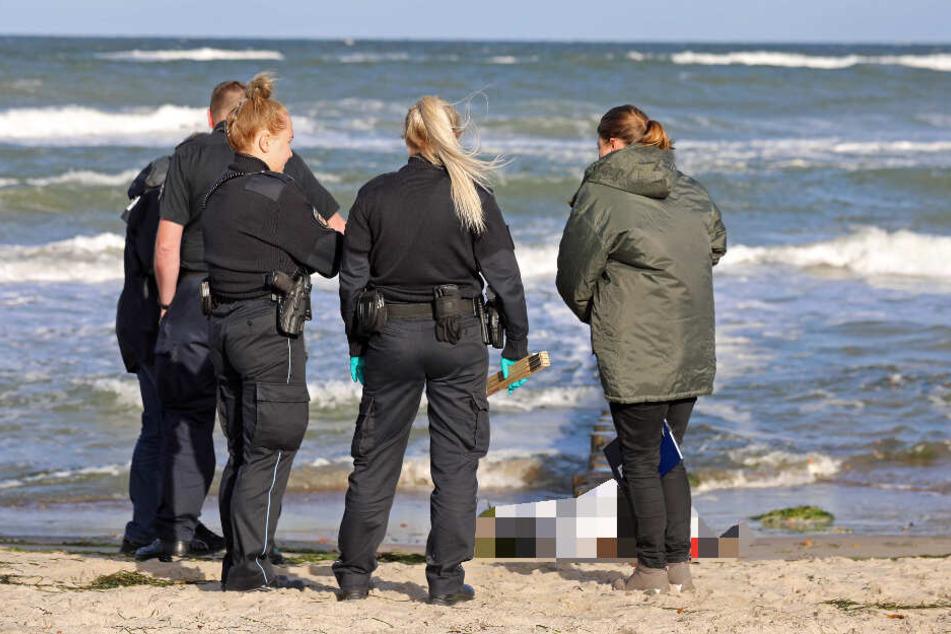 Polizisten untersuchen die Leiche am Ostseestrand.