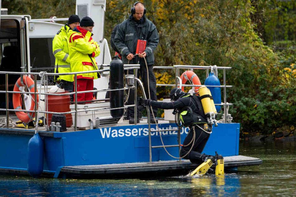 Ein Polizeitaucher geht ins Wasser, um nach dem Mädchen zu suchen.