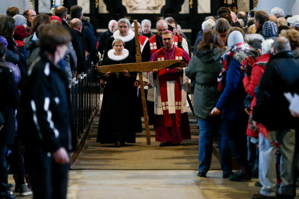 Bischöfin Kirsten Fehrs und Erzbischof Stefan Heße tragen vor dem Beginn des ökumenischen Kreuzwegs ein Holzkreuz durch die Jakobikirche.