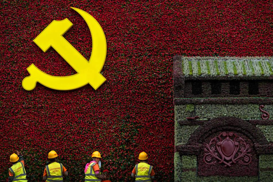 Peking: Arbeiter bringen Blumen an einer Dekoration mit dem Logo der Kommunistischen Partei an.