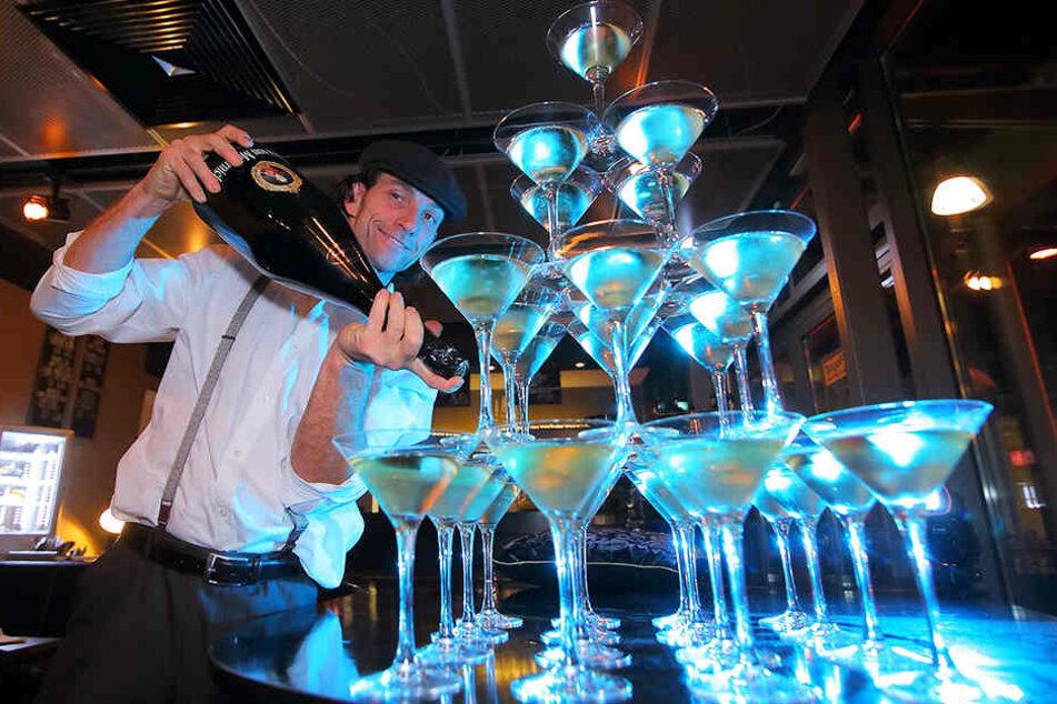 René Kuhnt (48) füllt aus der großen Sektflasche die Gläserpyramide auf.