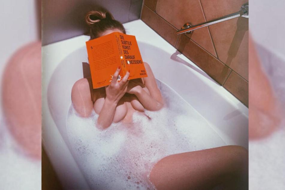 Playmate Annetta Negare liegt nackt in der Badewanne und verdeckt ihr Gesicht mit einem Buch.