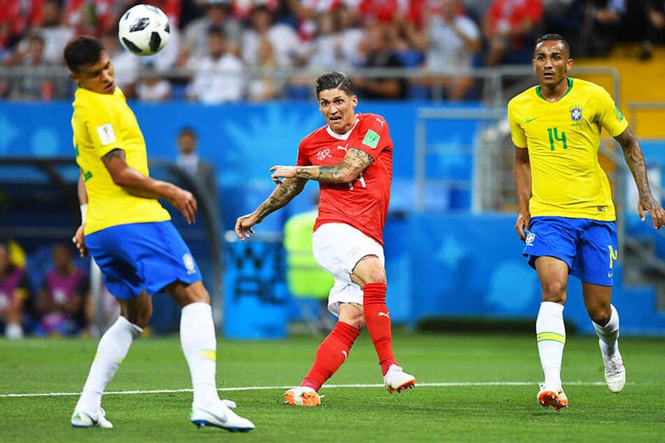 Der Schweizer Steven Zuber (m.) schießt Brasiliens Thiago Silva (l.) ab. Danilo (r.) schaut gebannt zu.