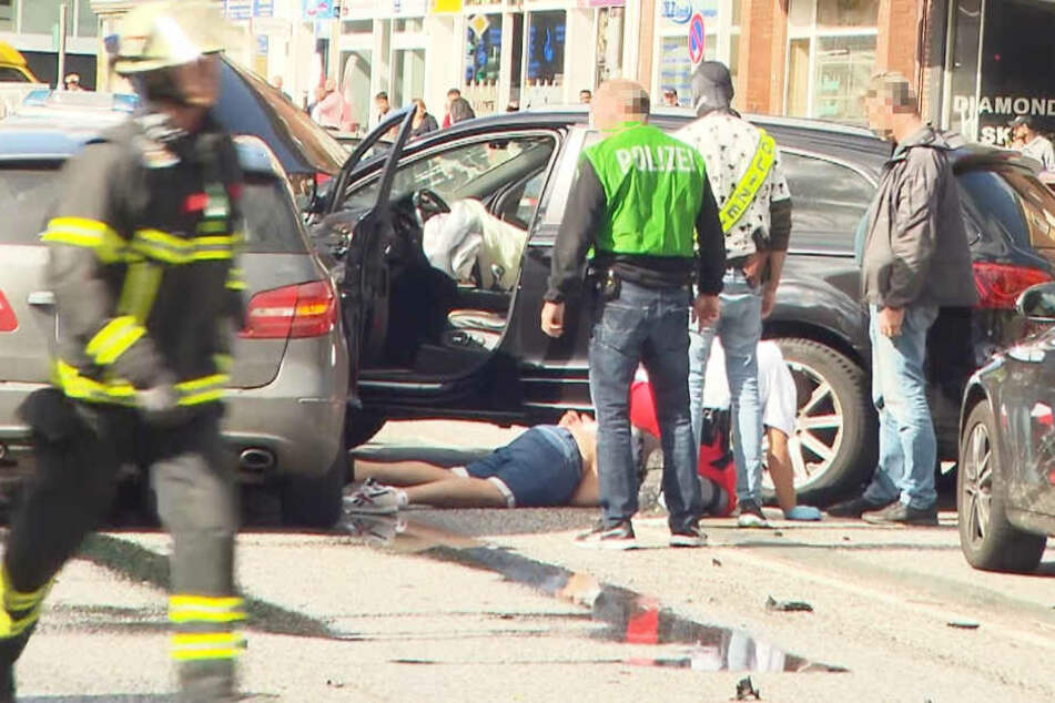 Zwischen den Unfallautos liegt ein festgenommener Mann auf dem Boden.