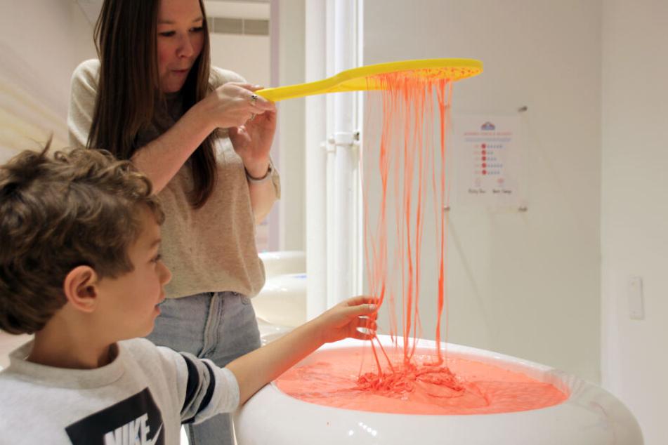 Eine Frau und ein Junge erkunden im Schleim-Museum (Sloomoo Institute) lachsfarbenen Schleim.