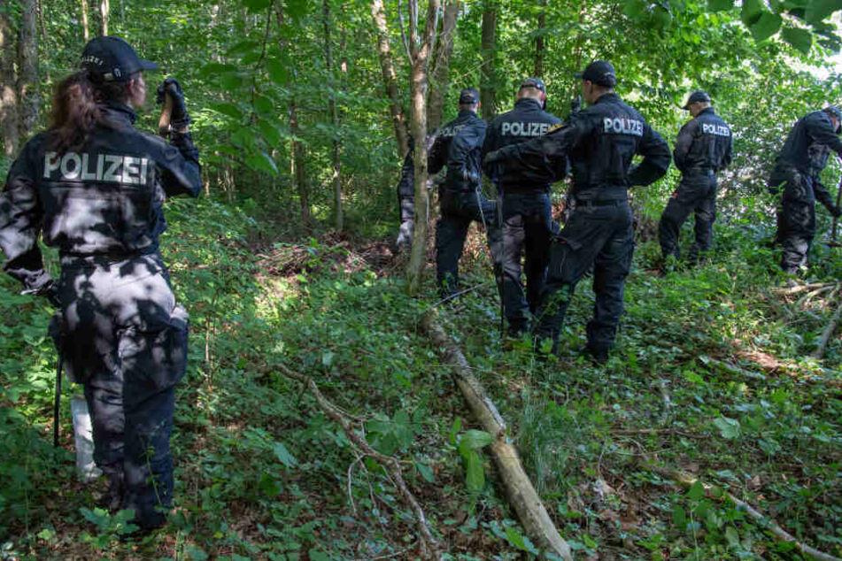 Polizisten suchen in einem Waldstück bei München nach zwei Leichen.