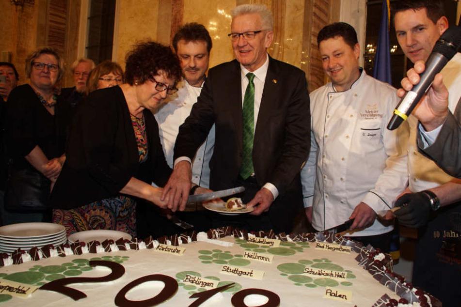 Winfired Kretschmann (Mitte) schneidet gemeinsam mit seiner Frau Gerlinde (links) eine Torte in Form des Bundeslandes Baden-Württemberg an.