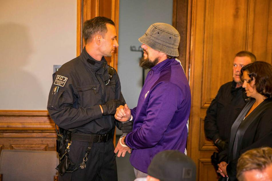 Marcus M. (36) wird von Justizbeamten in den Gerichtssaal geführt. Sein Verteidiger sieht keine Beweise dafür, dass er an den Gewalttaten direkt beteiligt war.
