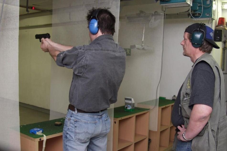 Ein Kunde zielt im Schießkeller mit einer Leihwaffe auf eine Scheibe, die Bahnaufsicht steht hinter ihm.