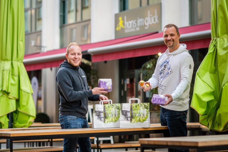"""Betriebsleiter Martin Kaufmann (30, l.) und Betreiber André Gruhle (46) packen die Speisen zum Abholen vom Burgergrill """"Hans im Glück"""" in Tüten."""