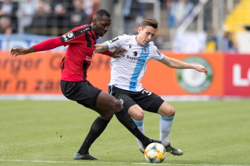 CFC-Riese Tarsis Bonga und TSV 1860 München-Spieler Phillipp Steinhart kämpfen um den Ball.