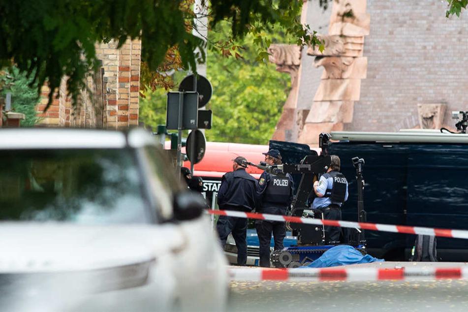 Polizisten sichern an der Mauer zur Hallenser Synagoge die Umgebung, die abgedeckte Leiche einer Frau liegt auf der Straße.
