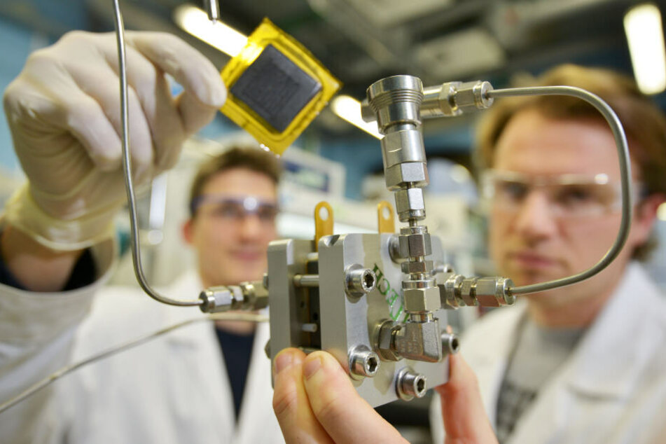 """Die TU-Chemiker Leonard Rößner (28, l.) und Benjamin Hentschel (28) zeigen eine Brennstoffzelle und ihr Kernstück, die """"Membran-Elektroden-Einheit."""""""
