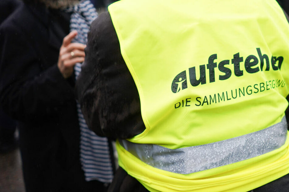 """Bei einer Aktion in Berlin im Januar 2019 trug ein Veranstaltungsteilnehmer eine gelbe Weste mit der Aufschrift """"aufstehen - die Sammlungsbewegung"""" ."""