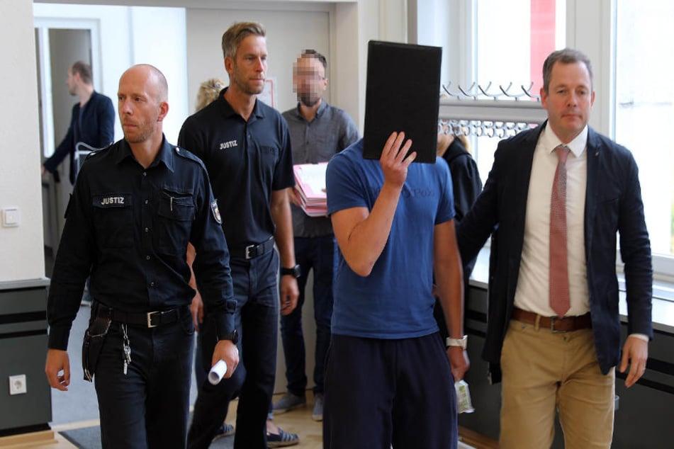 Einer der Angeklagten wird von zwei Beamten und seinem Anwalt (rechts) in den Gerichtssaal geführt.
