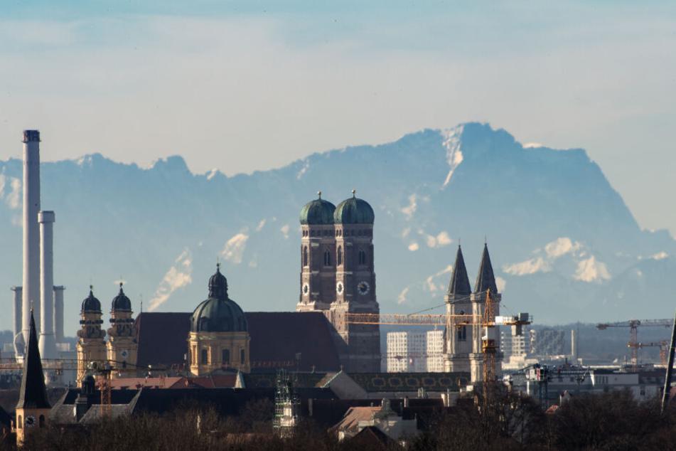 Die Skyline der bayerischen Landeshauptstadt ist vor der Kulisse der etwa 90 Kilometer entfernten Alpen mit der Zugspitze (rechte Bildhälfte) zu sehen.