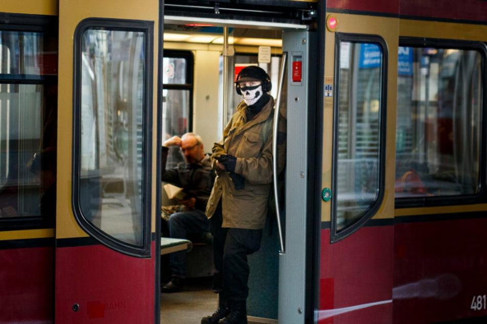 Ein Mann trägt in der S-Bahn im Bahnhof Alexanderplatz einen Munschutz auf dem Teile eine Totenkopfs abgebildet sind.