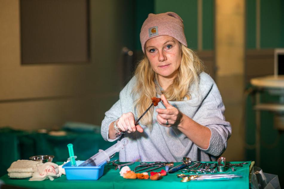 Sarah Zeising prüft in der OP-Kulisse die bereitliegenden chirurgischen Instrumente für die nächste Filmszene.