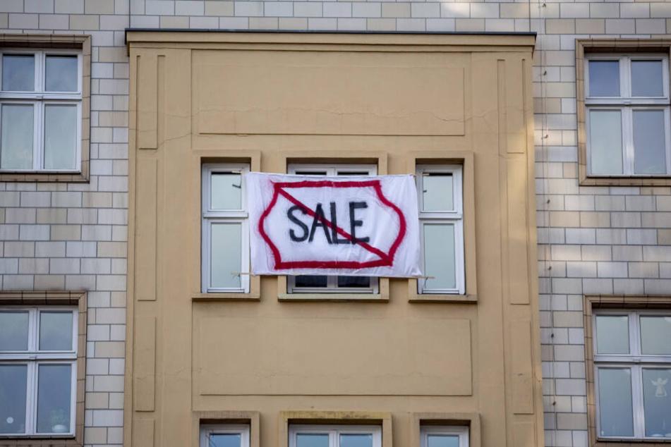 """Ein Plakat gegen den Verkauf von Mietwohnungen an die Deutsche Wohnen SE mit dem durchgestrichenen Wort """"Sale"""" hängt an einer Gebäudefassade in der Karl-Marx-Allee."""