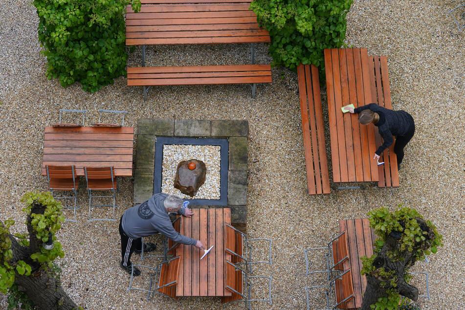 """Die Tische im Biergarten des Restaurants """"Maybach"""" im Stadtteil Eimsbüttel werden gereinigt. Hamburger Gastronomen dürfen ihre Außenbereiche wieder öffnen."""