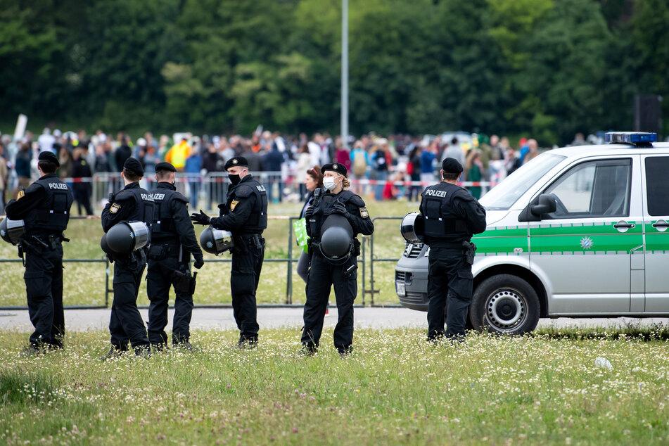 München: Teilnehmer einer Demonstration gegen die Anti-Corona-Maßnahmen der Politik stehen und sitzen auf der Theresienwiese im vorgeschriebenen Abstand.
